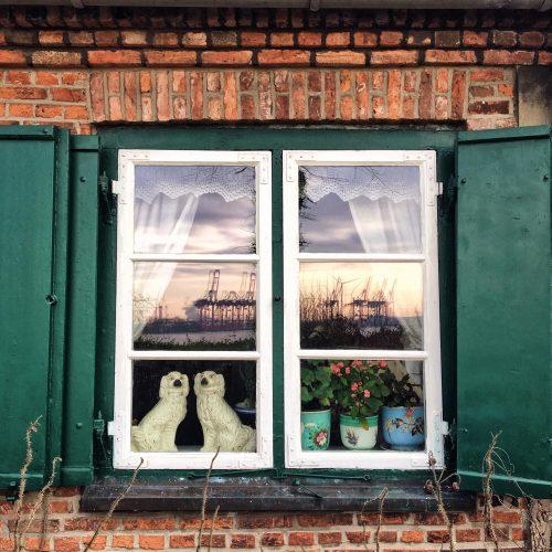 Puff-Hunde, Kaminhunde, Porzellanhunde im Fenster der Kapitänshäuser von Övelgönne Hamburg Frau Elbville